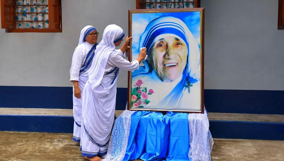 Nuns cleaning a portrait of Mother Teresa on the occassion of Mother Teresa's birthday.