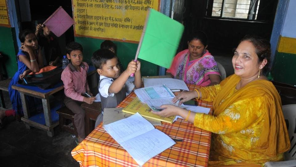 A student using a hand fan to get respite from heat at a primary school functioning without electricity for the last 20 years, in Kandhari Bazar in Lucknow.