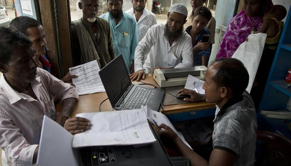 People check their names in the final list of the National Register of Citizens (NRC) and take out prints at an internet shop in Pabhokati village in Morigaon district of Assam, Saturday, Aug. 31, 2019.