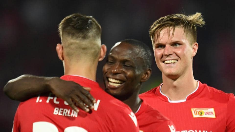 FC Union Berlin's Anthony Ujah, Robert Andrich and Marius Bulter celebrate after the match.