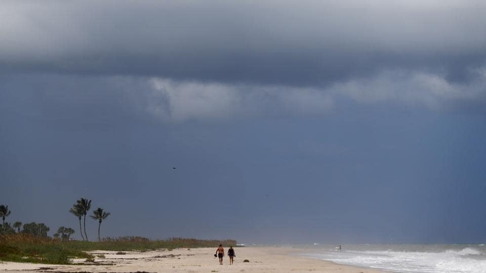 People walk on a largely deserted beach of the Atlantic Ocean on the barrier island in Vero Beach, Fla., on Sunday before Hurricane Dorian made landfall.