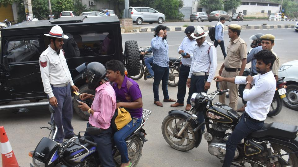 Traffic police personnel issue challans to those violating traffic rules at Maharana Pratap Chowk, in Gurugram.