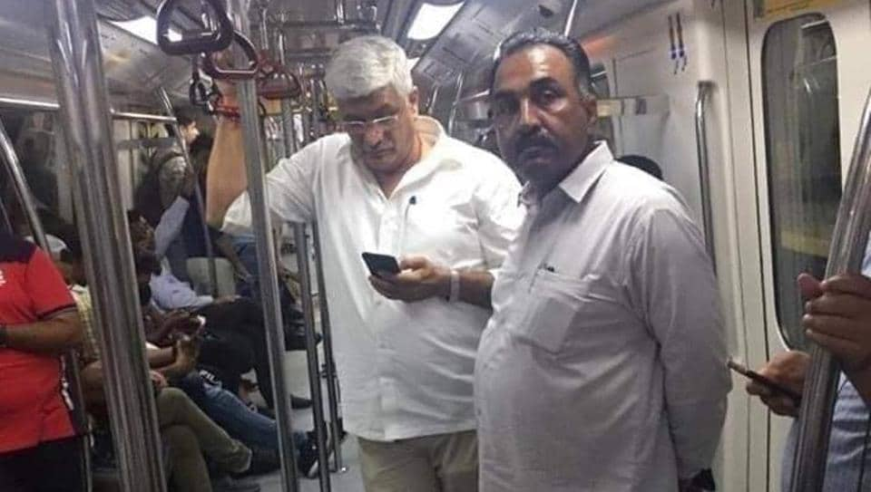 Gajendra Singh Shekhawat standing in Delhi metro with mobile in his hand.