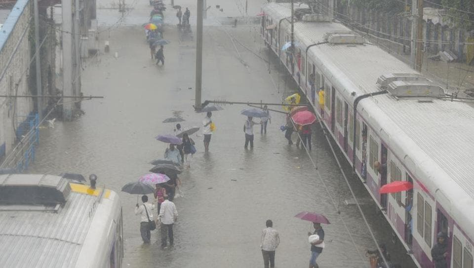 People walk on the railway track as trains stop working due to water logging on the railway track at Matunga (West) railway station in Mumbai.