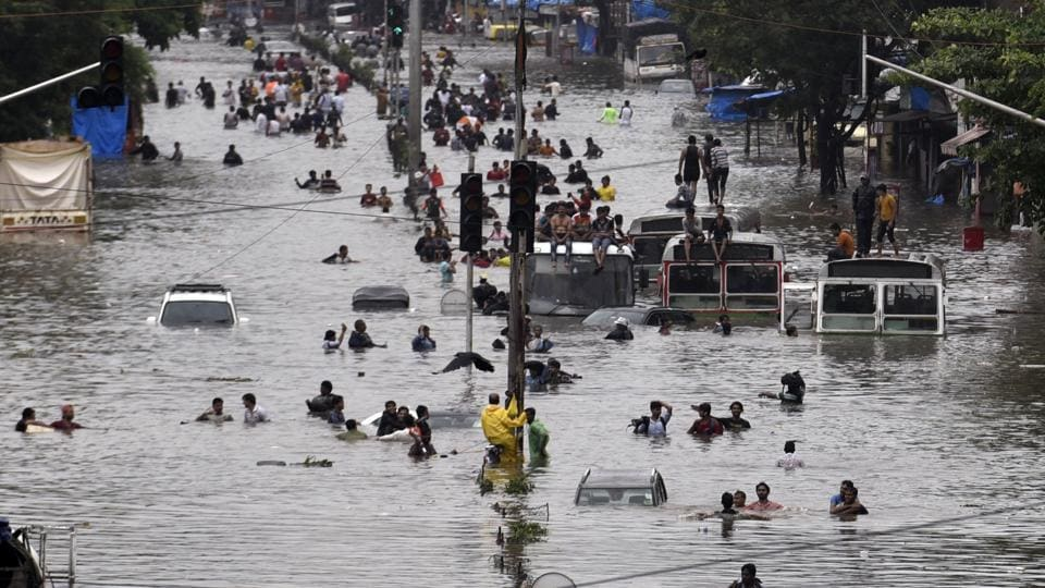 """People wade through a flooded street following heavy monsoon rains at LBS road Kurla in Mumbai. The India Meteorological Department (IMD) has predicted heavy rains in several parts of the city and suburbs in the next 48 hours. """"Mumbai most likely to get continuous rains and showers with the possibility of extremely heavy falls at isolated places in city and suburbs for the next 48 hours,"""" an IMD release read. (Kunal Patil / HT Photo)"""
