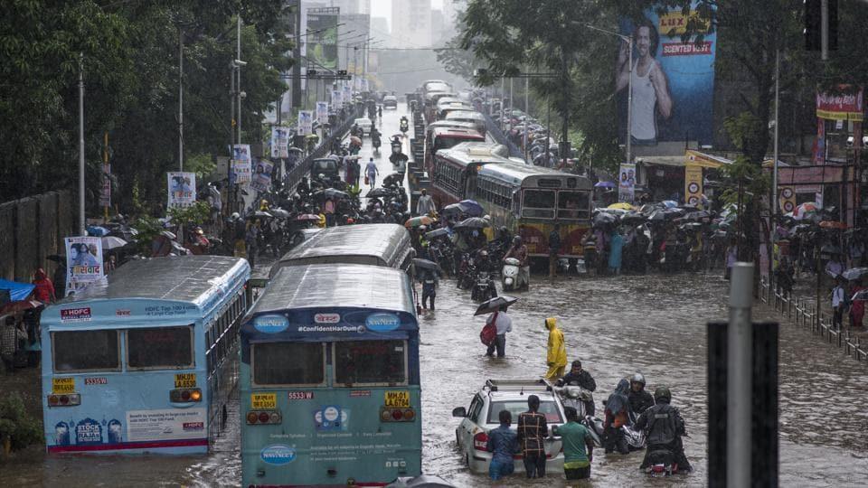 People and vehicles wade through flooded street at Dadar TT circle in Mumbai on Wednesday.