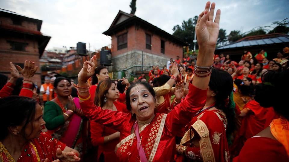 Women sing and dance at the premises of Pashupatinath Temple during Teej festival in Kathmandu, Nepal. The three-day festival involves sumptuous feasts and rigid fasting. Hindu women pray for marital bliss, the well-being of their spouses and children, and the purification of their own bodies and souls during this period. (Navesh Chitrakar / REUTERS)