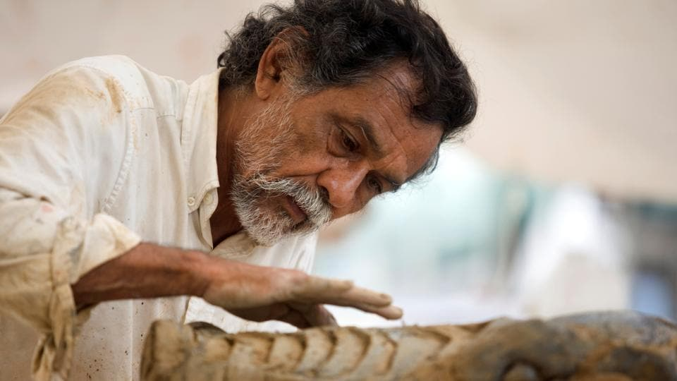 FILE PHOTO: Mexican graphic artist Francisco Toledo works on his sculpture 'La Lagartera', a 24.5 metre long giant reptile made of steel and plaster, in Monterrey, Mexico July 18, 2008. REUTERS/Tomas Bravo/File Photo