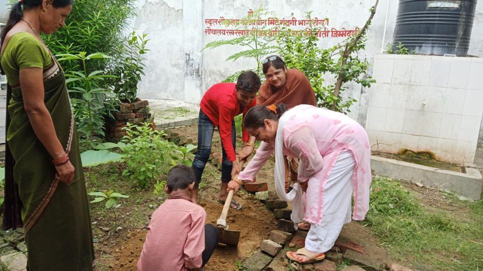 Teacher and children in a kitchen garden in government primary school, Rasulabad, in Prayagraj