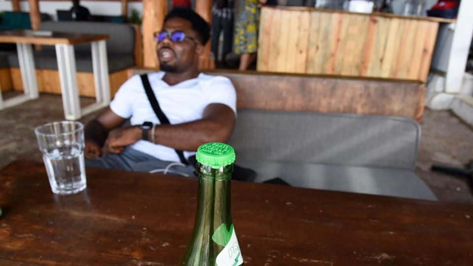 "A man sits on a couch by a bottle with a collected capsule laying on a table at the Copacabana restaurant. ""Every action counts,"" Thiaw said. ""When you know that a plastic bottle takes up to 1,000 years to decompose, how can you not use glass bottles? (Seyllou / AFP)"