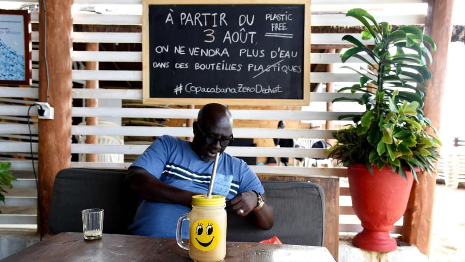 "A customer sits on a couch in front of a glass with a metallic straw at the in Copacabana restaurant. President Macky Sall, sworn in for his second term in April, has proposed turning Senegal into a ""zero waste"" nation. Untreated effluent goes straight into the ocean and plastic debris is a chronic problem, often covering shorelines as far as the eye can see. (Seyllou / AFP)"
