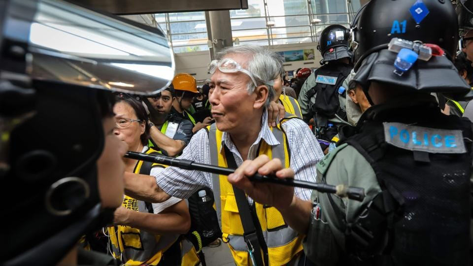 """Grandpa Wong"" (C), 85, shields protesters from the police by holding his walking stick up along with other ""silver hair"" volunteers in the Tung Chung district in Hong Kong. ""I'd rather they kill the elderly than hit the youngsters,"" he told AFP during a recent series of skirmishes in the shopping district of Causeway Bay, a gas mask dangling from his chin. (Vivek Prakash / AFP)"