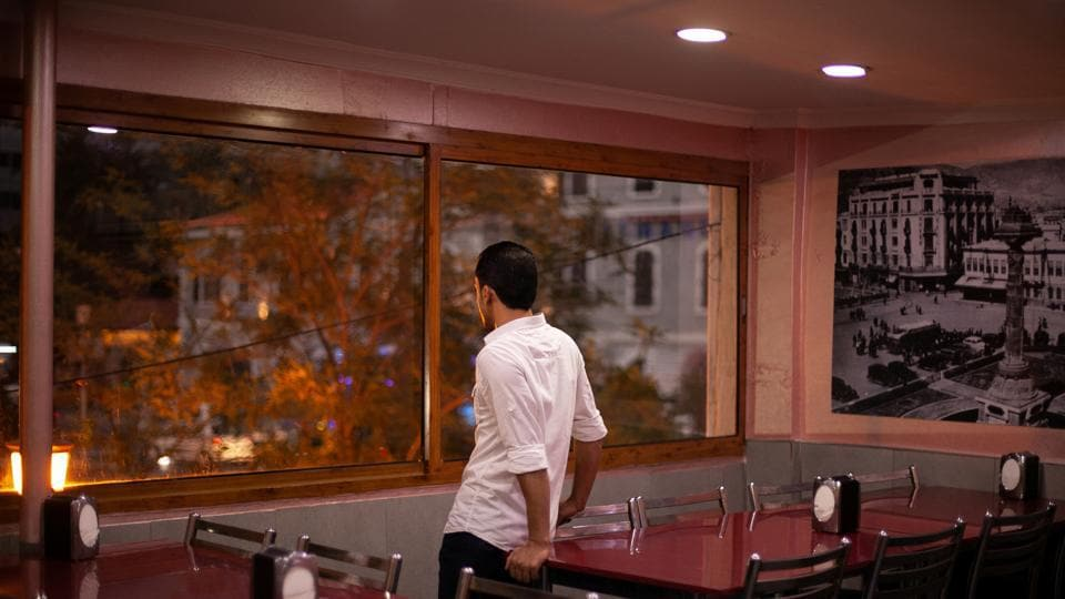 "Ahmed looks out from a window in a Syrian restaurant popular among refugees in Izmir. ""Maybe these are signs that we should not go,"" Ahmed would sometimes say in the lead-up to their 2018 attempt. ""Every new problem is trying to say something to us."" But he saw no option but to leave Turkey, because staying meant he would ""keep working in that factory forever"". (Ekaterina Anchevskaya / REUTERS)"