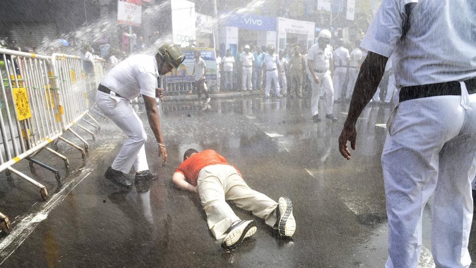 Cops use water cannon on BJYM activists during their protest against the high rate of electricity bills, in Kolkata. A BYJMactivist lies down on the road after intake of water from the water cannon.
