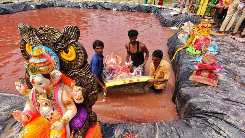 Municipal workers in Delhi help residents immerse idols in an artificial water body. In a bid to reduce the pollution load on the Yamuna river, the Delhi Pollution Control Committee (DPCC) had asked puja organisers to immerse the idols in 129 artificial ponds built at designated sites across the city. (Raj K Raj / HT Photo)
