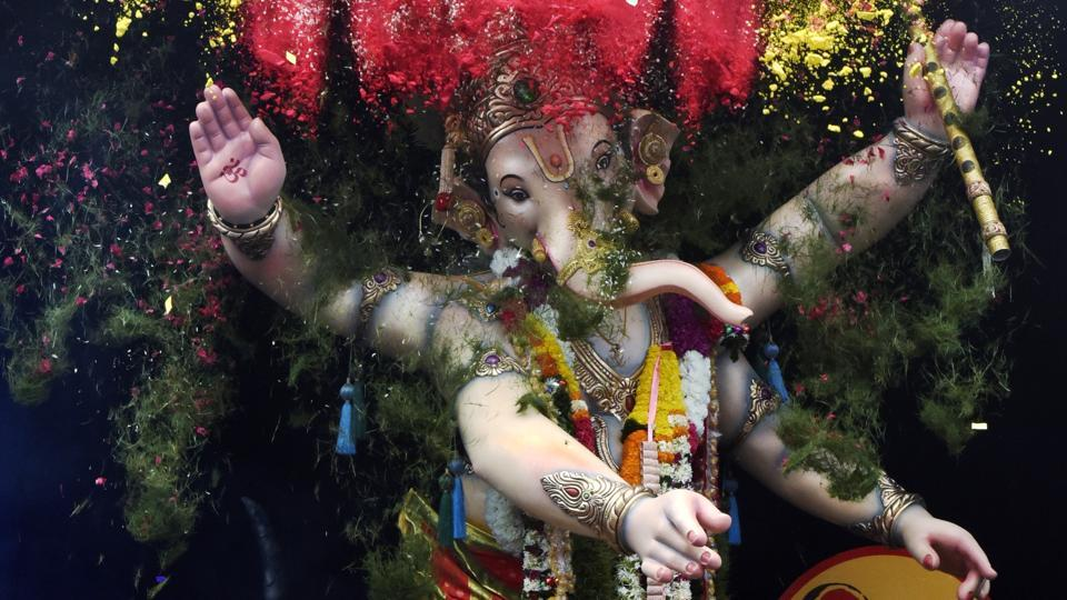 Confetti, flower petals and coloured powder are showered on an idol of the Hindu deity Ganesha during a procession at Marine Lines in Mumbai. The immersion of Ganesha idols amid chants of Ganpati Bappa Moraya, Pudhchya Varshi Lavkar Ya (come back soon next year) today, mark the end of festivities making the 10 day Ganesh Chaturthi festival. (Kunal Patil / HT Photo)