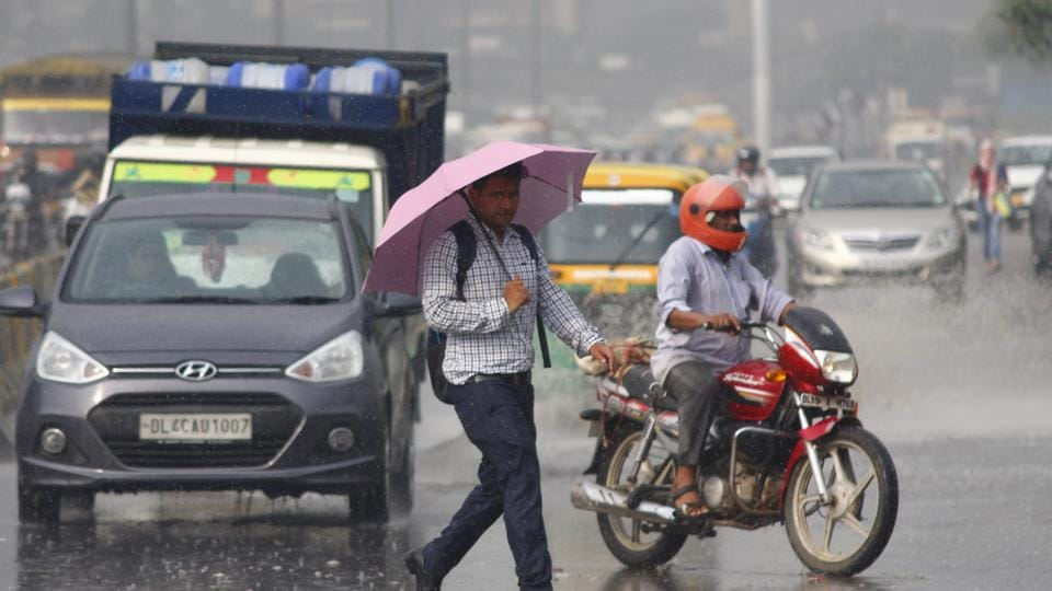 People move during light rain, at National Highway 48, Sector 30, in Gurugram, India, on Thursday, September 12, 2019. (Photo by Yogendra Kumar / Hindustan Times)