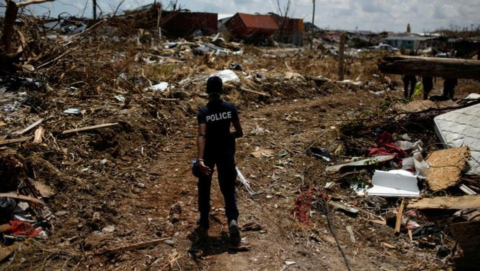 A police officer searches for the dead in a destroyed neighborhood after Hurricane Dorian hit the Abaco Islands in Marsh Harbour, Bahamas.