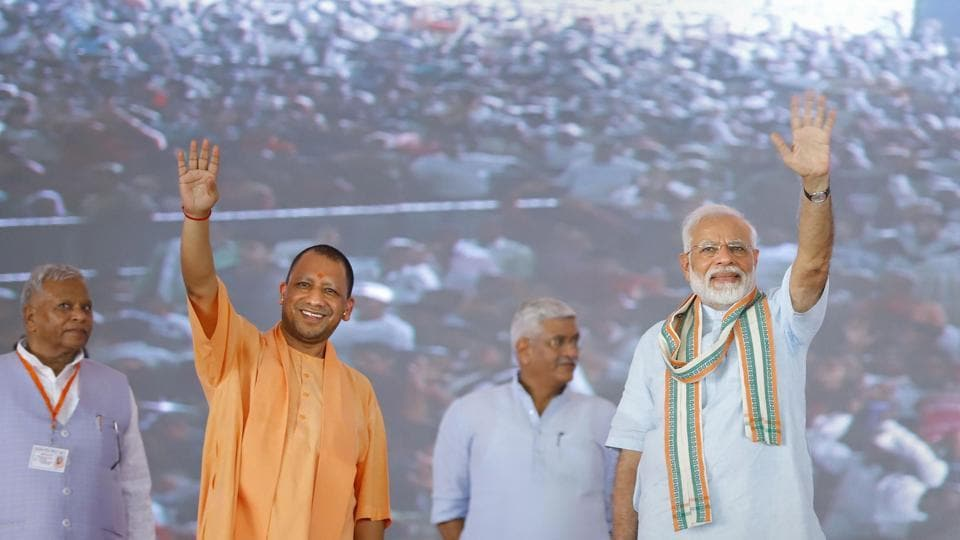 Prime Minister Narendra Modi and Uttar Pradesh Chief Minister Yogi Adityanath wave at their supporters during launch of National Animal Disease Control Programme for eradication of Foot and Mouth Disease and Brucellosis in livestock, in Mathura, Wednesday, Sept. 11, 2019.