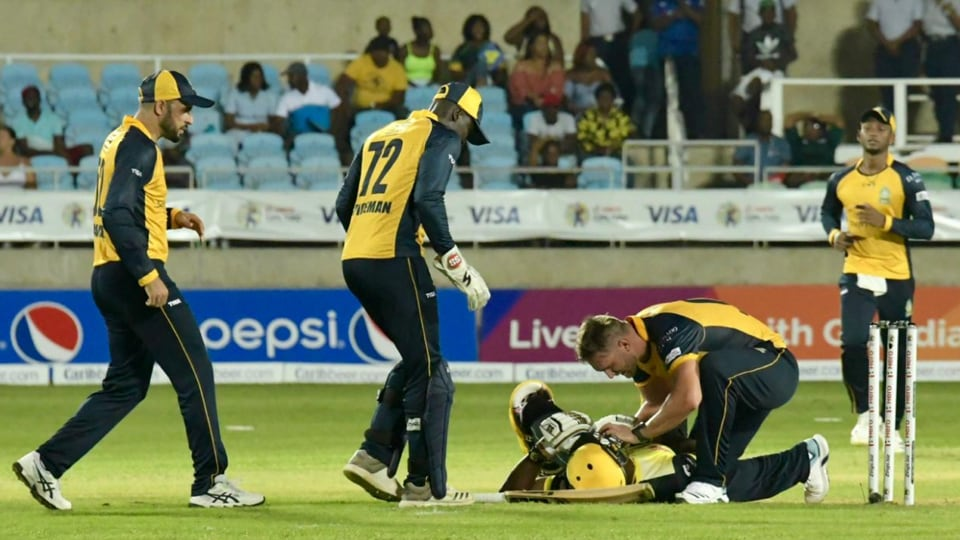 Andre Russell falls on the ground as opposition players come in to check.