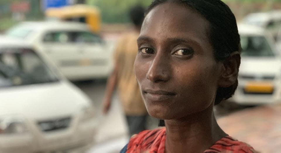 Sakeena, a resident of Central Delhi's Sarai Kale Khan, works as an unofficial parking attendant alongside a busy avenue.