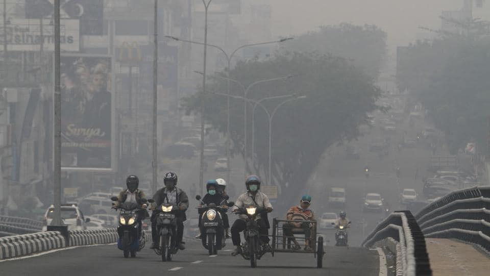 "Motorists ride through a road blanketed by haze from wildfires in Pekanbaru. In 2015 Indonesia suffered its worst forest fires for almost two decades, which dramatically increased its greenhouse gas emissions. Diplomatic tensions were also rising as Malaysian Environment Minister Yeo Bee Yin accused her Indonesian counterpart of being ""in denial"", after Jakarta insisted fires in Malaysia had caused the smog there. (AP)"