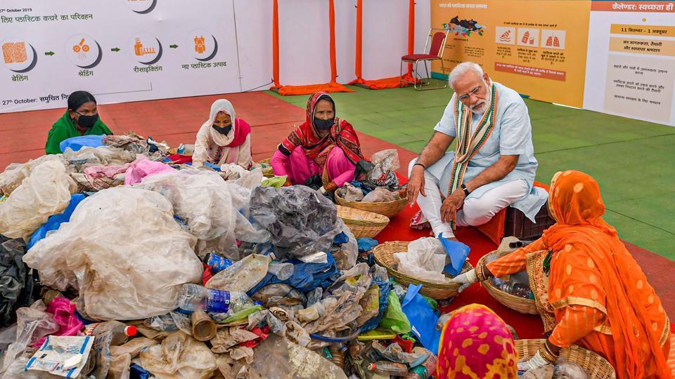Prime Minister Narendra Modi assists women segregate plastic waste under 'Swachhta Hi Seva' programme in Mathura.