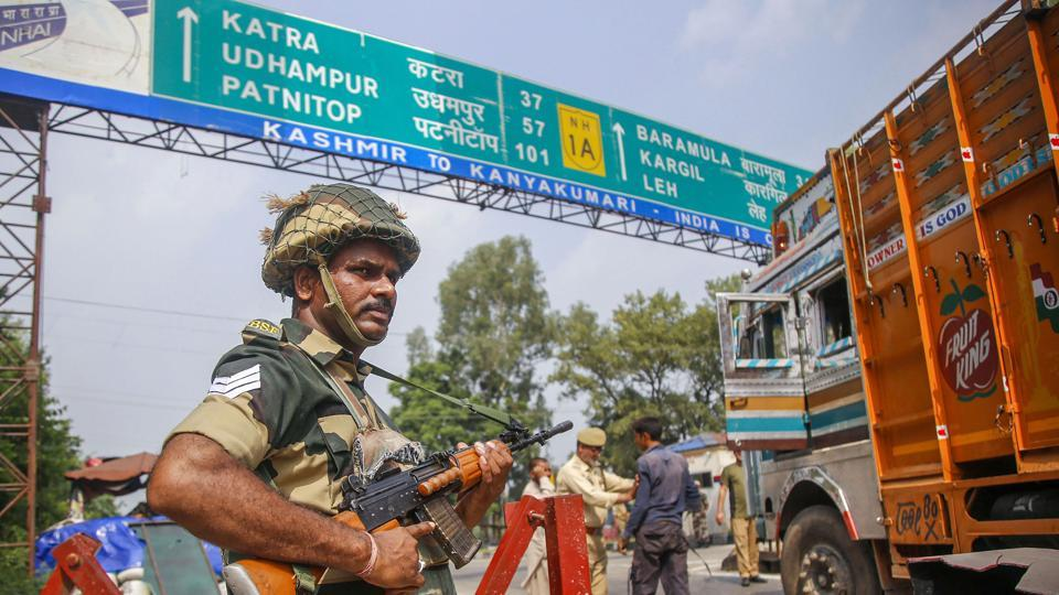 A BSF jawan guards as Jammu and Kashmir Police personnel check the vehicles on the Jammu-Srinagar highway.