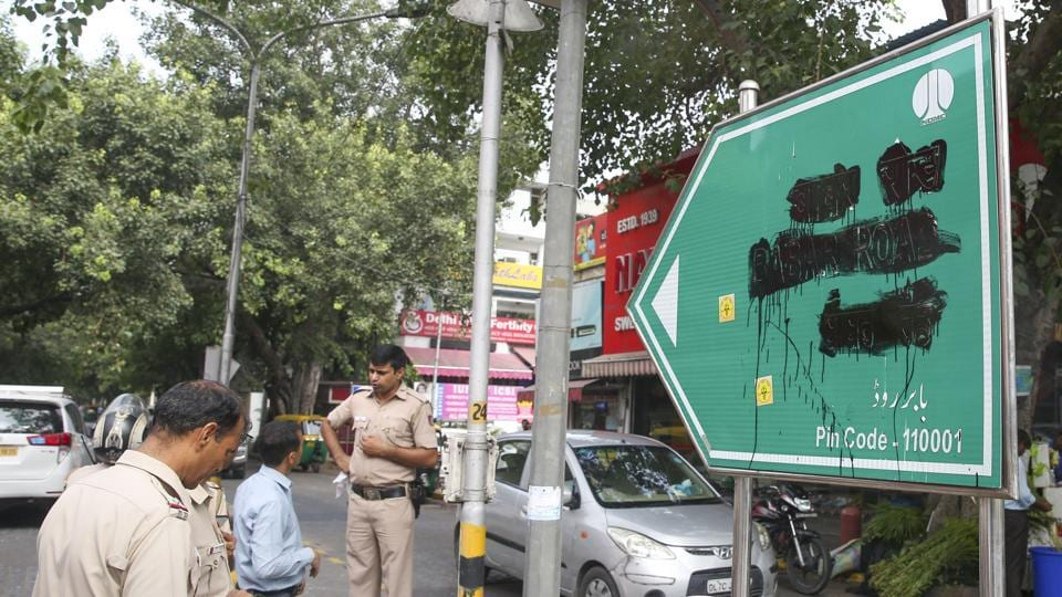 Police personnel stand beside the blackened signboard for Babar Road in New Delhi on Saturday. Right-wing outfit Hindu Sena blackened the signage in Bengali market demanding that it be renamed.