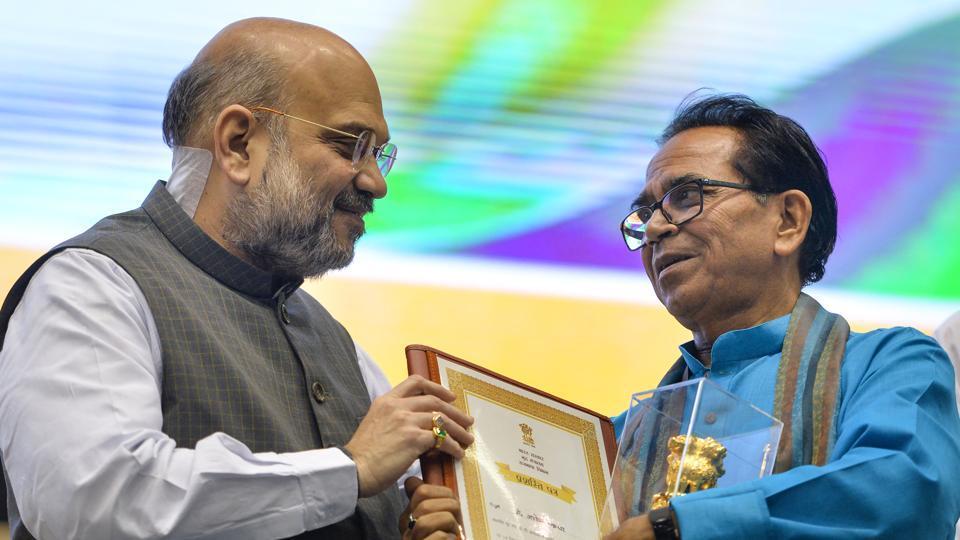 Home Minister Amit Shah presents an award to author Ashok Chakradhar during the 'Hindi Divas Samaroh' in New Delhi, Saturday, Sept. 14, 2019.