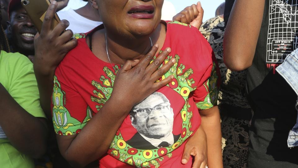 Supporters of Zimbabwe's former president Robert Mugabe react upon the arrival of his mortal remains at RG Mugabe airport in Harare. As controversy continues around the burial of Mugabe, the capital, Harare, bustles with people coping with the challenges of daily life amid widespread shortages. (Tsvangirayi Mukwazhi / AP)