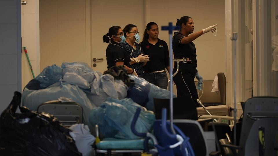 Hospital employees work next to medical equipments at the Badim Hospital, where a fire left at least 11 people dead, in Rio de Janeiro, Brazil on Friday. The fire raced through the hospital forcing staff to wheel patients into the streets on beds or in wheelchairs.