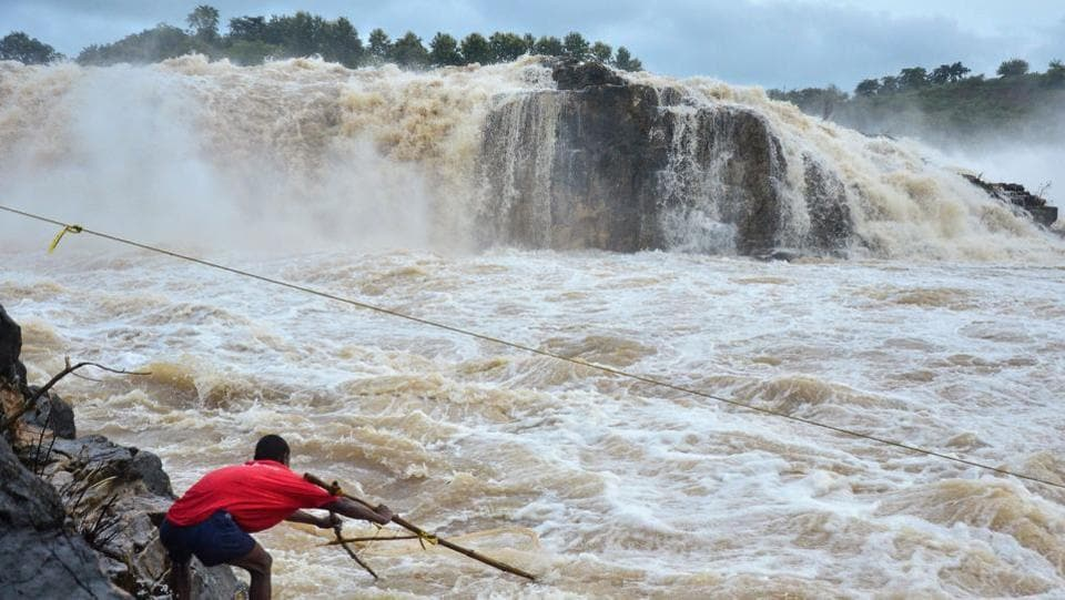 A fisherman uses a net attached to sticks to catch fish in rough waters next to Dhuandhar Falls following heavy rainfall, at Narmada River, in Jabalpur, Madhya Pradesh. (Shankar Mishra / AFP)
