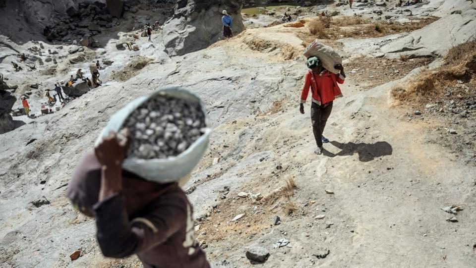 "Workers from the Father Opeka's association Akamasoa carry stones and grabble from a Granite quarry. The town's white walls contrast with the filth of Antananarivo's streets. Painted slogans say ""No speaking, we are working."" (Gianluigi Guercia / AFP)"