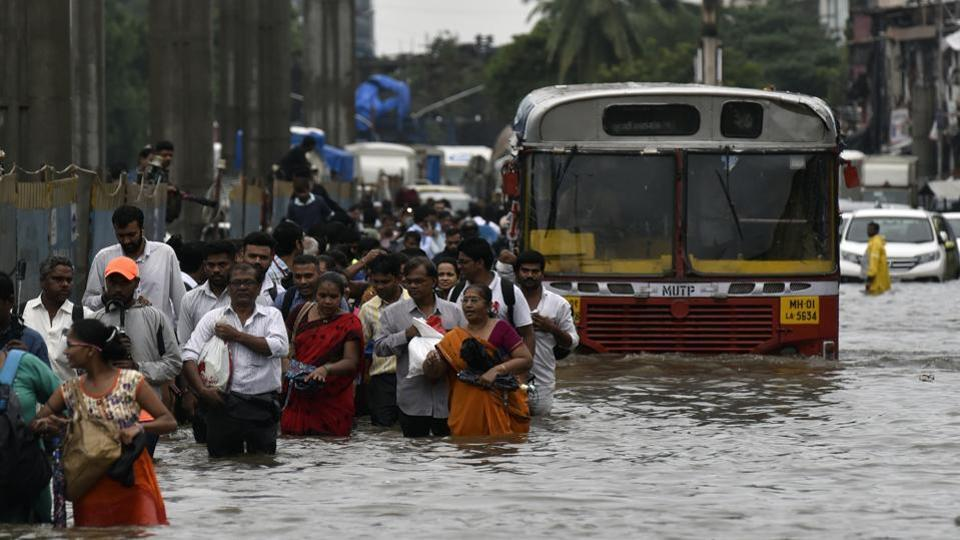 People walk through a flooded street following heavy monsoon rains at LBS road Kurla in Mumbai.