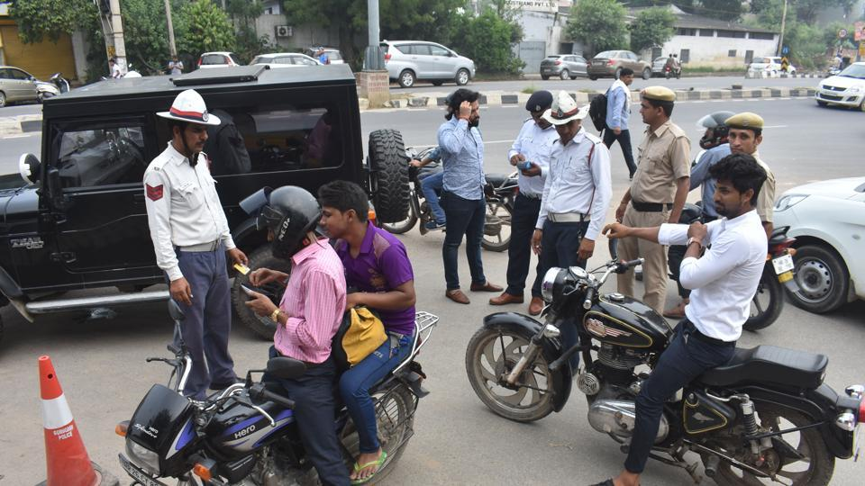 Traffic police personnel issue challans to traffic rules violators at Maharana Pratap Chowk, in Gurugram.