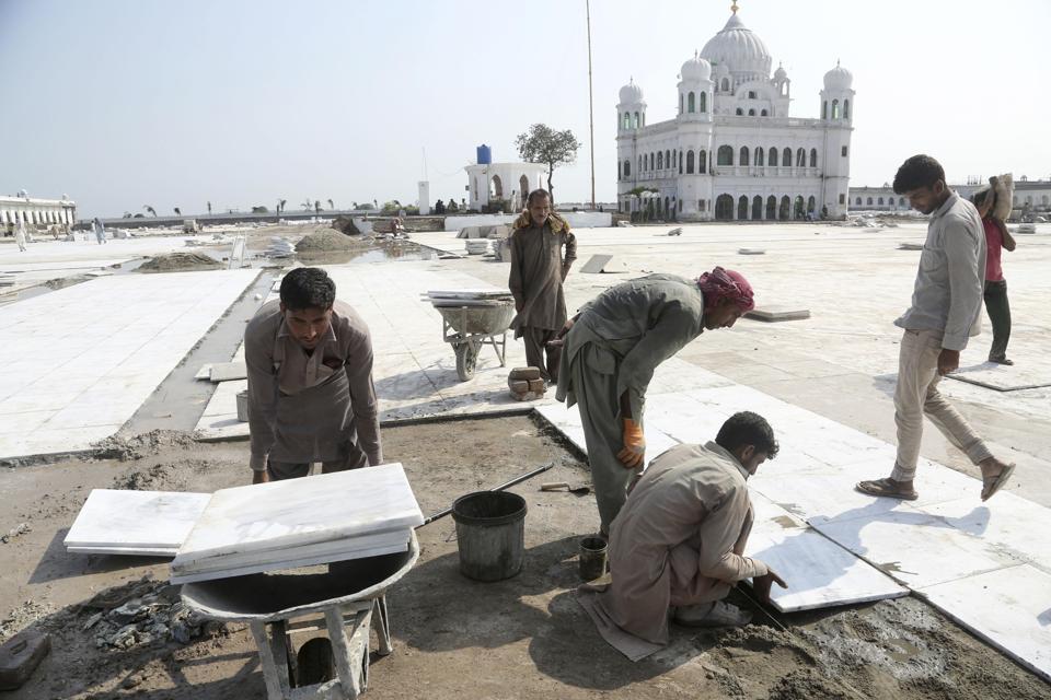 Pakistani workers give finishing touches to the shrine of Sikh spiritual leader Guru Nanak Dev, in Kartarpur, Pakistan.