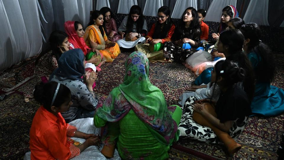 "Women sing at a marriage ceremony. The marketing manager had originally planned a three-day extravaganza, including a make-up session, music, and a huge canopy to accommodate more than 700 guests invited to partake in the traditional Kashmiri wazwan feast. ""I grew up dreaming about a grand wedding but there is not much to celebrate because of the situation,"" the 29-year-old told AFP. (Tauseef Mustafa / AFP)"