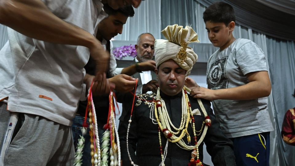 "A groom is garlanded by relatives and friends before leaving for his bride's home in Kashmir's Baramulla. Parents start preparing for their child's marriage almost immediately after birth, Bilal said. So when only 15% of the invited guests turned up for his brother's wedding last month, ""it was a heartbreak for the family,"" he said. (Tauseef Mustafa / AFP)"