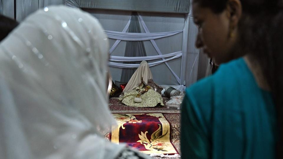 Guests look at a bride (C) with her face and body covered with a shawl sits in her new husband's home following their marriage. For bride-to-be Nisar, her September wedding to her boyfriend of five years came after a hard-fought battle with their parents to overcome resistance to the marriage. (Tauseef Mustafa / AFP)