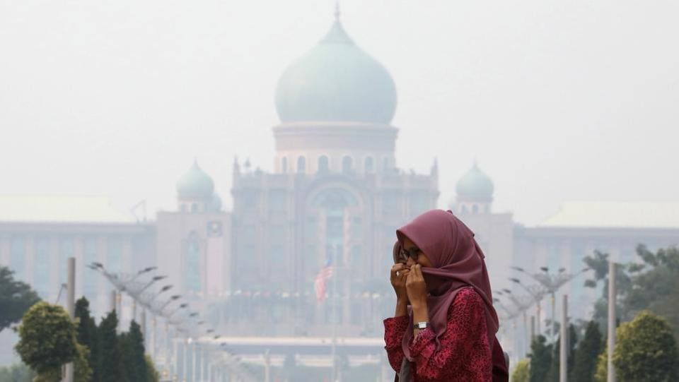A woman covers her face with a scarf in front of the Malaysia's Prime Minister's office. Nearly every year, Indonesian forest fires spread health-damaging haze across the country and into neighboring Malaysia and Singapore. The fires are often started by smallholders and plantation owners who set land on fire as a cheap way of clearing it for new planting. (Lim Huey Teng / REUTERS)