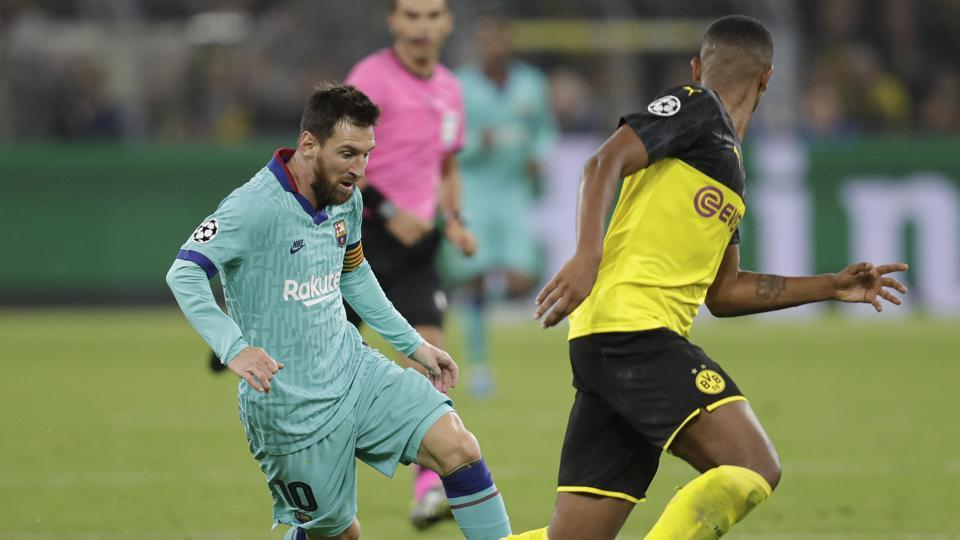 Barcelona's Lionel Messi challenges for the ball with Dortmund's Manuel Akanji during the Champions League Group F soccer match between Borussia Dortmund and FC Barcelona in Dortmund, Germany, Tuesday, Sept. 17, 2019.