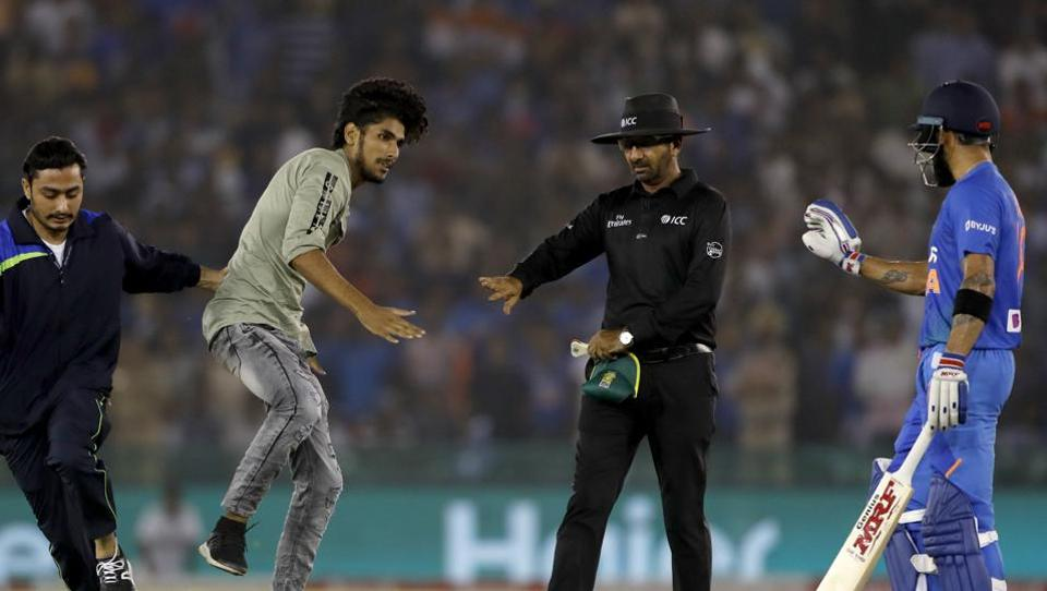 A security personnel, second from left, tries to stop a fan of India's captain Virat Kohli.