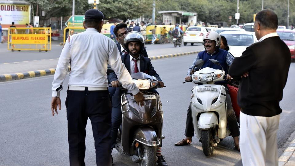 Traffic Police issues challan for driving without helmet at Barakhamba Road, Connaught Place, in New Delhi, India.