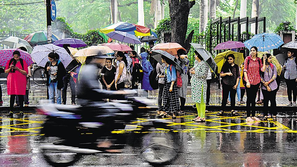 A respite from gloomy wether are the colourful umbrellas which residents use to protect themselves from the heavy rains at the JM road bus stop on Wednesday.