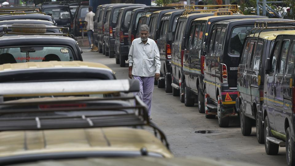 A commuter walks past the parked taxis during a strike call by United Front of Transport Associations against the hefty penalities for road traffic violations under the amended Motor Vehicles Act, at Nizamuddin Railway Station, in New Delhi, India, on Thursday, September 19, 2019.