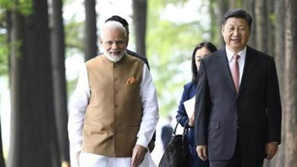 Prime Minister Narendra Modi and Chinese President Xi Jinping walk together in Wuhan in central China's Hubei Province during the April 2018 bilateral.
