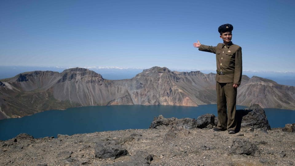 "A North Korean student poses for a photo at the summit of Mount Paektu. The visiting troupes sing songs such as ""We Will Go to Mount Paektu"" and paddle joyously in Lake Chonji, its crater lake. ""Everyone needs a spiritual pillar,"" said Ri Yong Myong, 30, who is studying Korean literature at the elite Kim Il Sung University in Pyongyang after 10 years of military service. (Ed Jones / AFP)"