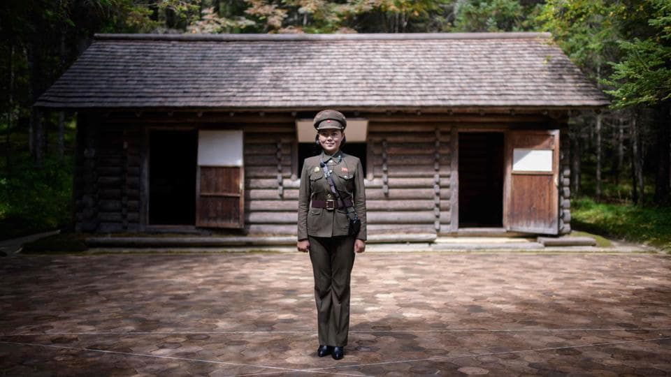"Guide Kim Un Sim (23) poses for a portrait before a replica of the cabin said to be used by Kim Il Sung at the 'Secret Camp', said to be the birthplace of late North Korean leader Kim Jong Il, near Samjiyon. North Korean leader Kim Jong Un's father and predecessor is said to have been born in a simple wooden hut on the slopes of a sacred mountain, and guide Kim Un Sim has no doubts: ""Welcome to our holy land."" (Ed Jones / AFP)"