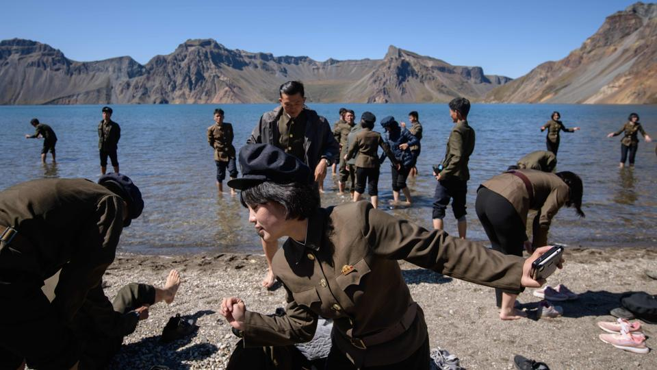 "North Korean students stand in Chonji lake, or 'Heaven lake', as they visit the crater of Mount Paektu. ""Rather than wealth or honour, the Korean people hold Mount Paektu, which is the holy mountain and the mountain of our great leaders, as our spiritual pillar. My body is full of the spirit and force of Mount Paektu so I can provide loyal service to the leader by even grinding all my bones and flesh,"" Ri said. (Ed Jones / AFP)"